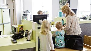 Äiti lapsineen lääkäriaseman vastaanottotiskillä Helsingissä keskiviikkona 9. syyskuuta 2015.