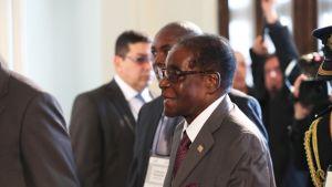 Zimbabwen presidentti Robert Mugabe seisoo miesten keskellä.