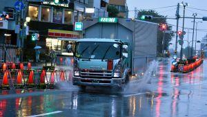 Kuvassa katunäkymä, kuorma-auto ajaa vesilätäköiden yli