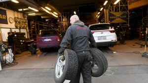 Asentaja kantaa auton renkaita.