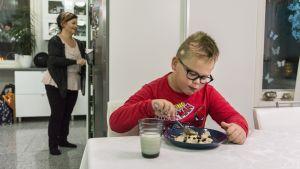 Otso Soini syö aamupuuroa keittiön pöydän ääressä.