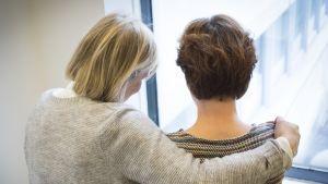 Kaksi naista seisoo ikkunan edessä ja toisen käsivarsi toisen hartioiden ympärillä.