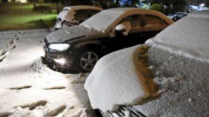 Lumen peittämiä autoja parkkipaikalla.