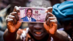 Mies pitelee kädessään Odingan kuvalla varustettua, väärennettyä 1000 shillingin seteliä.