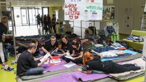 Ihmisiä istuu retkipatjojen päällä lattialla. Heillä on käsissään papereita.
