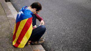 Katalonian lippuun kääritynyt mies istuu kadulla ja käyttää puhelintaan.