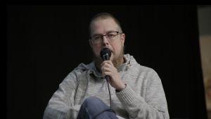 Kirjalija Tuomas Kyrö istuu lavalla kädessään mikrofoni.