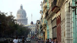 Ihmisiä kävelee kadulla Havannassa, Kuubassa. Kadun varrella on värikkäitä taloja.