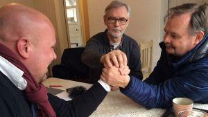 Miehet ovat vääntävinään kättä.