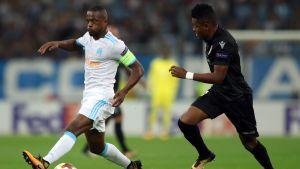 Patrice Evra pitää palloa, Jubal of Vitoria Guimaraes jahtaa.