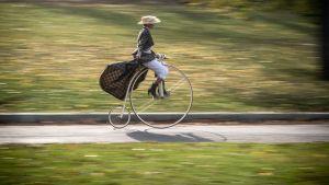 Historialliseen asuun pukeutunut nainen ajoi vuosittaisessa pyöräkisassa penny-farthing -polkupyörällä Prahassa, Tšekissä 4. marraskuuta.
