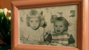 Pitsiliinan päällä kehystetty kuva kahdesta pikkutytöstä, jotka pitävät toisiaan kädestä kiinni.