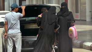 Naiset ottamassa lastenrattaita ulos autosta ostoskeskuksen parkkipaikalla Riadissa 27. syyskuuta.