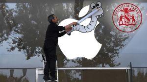Aktivisti kiinnittää matoa Applen omena-logoon Ranskassa.