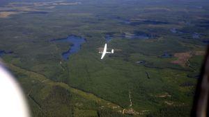 ilmakuva, jossa purjelentokone lentää metsien ja järvien yllä.