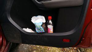 Limsapullo ja irtokarkkipussi auton ovikotelossa