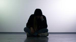 Mustaan huppariin pukeutunut nuori istuu pää painuneena jalat ristissä.