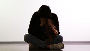 Huppariin pukeutunut nuori pitkätukkainen istuu pää painuksissa.