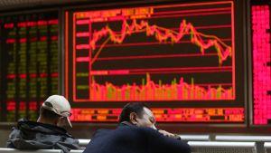 Kaksi miest istuu arvopaperimarkkinoiden kehitystä kuvaavan näyttöruuden edessä.