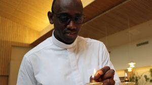 Pyhän Ursulan seurakunnan kirkkoherra Jean Claude Kabeza sytyt kynttilaa