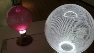 pyöreitä raidallisia lasipalloja joiden sisällä on valo