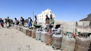 Jemeniläisiä miehiä jonottamassa tyhjien kaasutynnyrien kanssa Sanaassa.