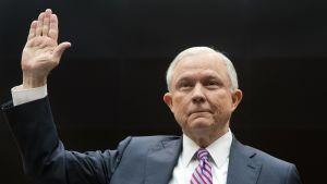 Jeff Sessions mustaa taustaa vasten kuvattuna. Sessionsilla on yllään tummanharmaa puku. Hän pitää oikeaa kättään ylhäällä vannoessaan todistajanvalaa.