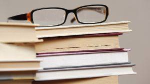 Kirjapino, jonka päällä silmälasit.