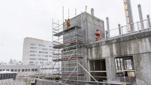 Miehiä tellingeillä sairaalan rakennustyömaalla.