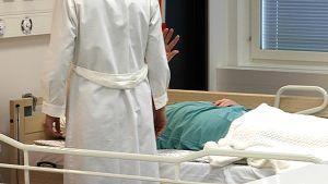 Sängyssä makaava potilas koskettelee henkilökuntaa