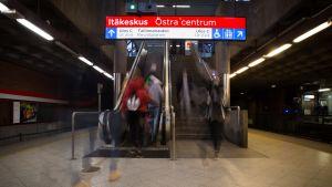 Ihmisiä menee metrolaiturilta rullaportaisiin.