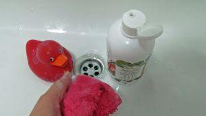 Kylpyankka ja suihkuvaahtopullo kylpyammeen pohjalla. Kädessä pesulappu, jossa saippuavaahtoa.