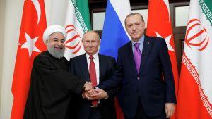 Hasan Rouhani, Vladimir Putin ja Recep Tayyip Erdoğan pitävät käsiään yhdessä ja poseeraavat kameralle maidensa lippujen edessä.