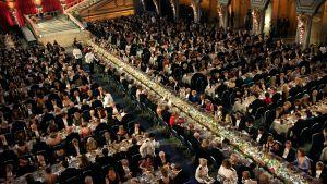 Suuressa salissa pitkiä pöytiä joissa istuu ihmsiä.