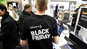 Kodinelektroniikkaketju Gigantin työntekijällä on päällään paita jossa mainostetaan Black Fridayta.
