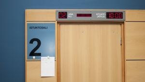 Käräjäoikeuden istuntosalin ovi, jonka takana istunto meneillään.