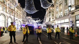 Kuvassa kuusi poliisia keltaisissa asuissaan rivissä Oxford Streetin jouluvalojen alla.