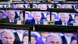 Vladimir Putin näkyy useassa televisiovastaanottimessa elektroniikkaliikkeesssä.