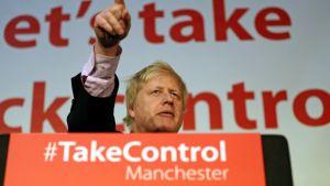 Boris Johson osoittaa puhujakorokkeelta sormella yleisöä. Puhujapöntössä on teksti, joka kehottaa ottamaan vallan itselle.