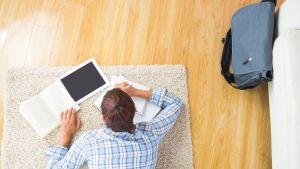 Opiskelija makaa mahallaan lattialla ja kirjoittaa muistiinpanoja.