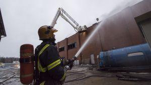 Palomies sammuttaa tehdaspaloa.