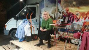 Nainen istuu tuolilla värikkääksi maalatun asuntoauton edessä.