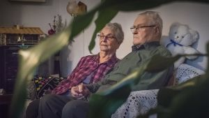 Pariskunta istuu sohvalla käsi kädessä.
