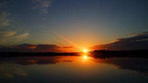 Kuvassa auringonlasku järven rannalla.