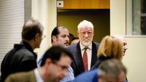 Bosnian kroaattijoukkoja 1990-luvulla komentanut Slobodan Praljak saapui oikeuteen Haagissa Hollannissa 29.11.2017. Harmaatukkainen Praljak kuvassa ihmisjoukon keskellä.