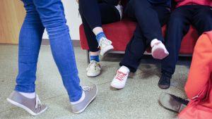 Oppilaita koulun käytävällä, kuvassa nuorten kenkiä.