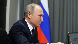 Putin istuu pöydän ääressä tummassa puvussa, musta kravatti kaulassaan. Putinin oikea käsi nojaa pöytään ja pitelee lyijykynää. Taustalla näkyy Venäjän lippu ja salin harmaanvihreää verhoa.