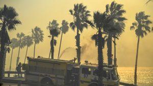Paloauto etualalla savun kellertäväksi värjäämässä merenrantamaisemassa; rannan palmuja kohti suihkutetaan vettä.