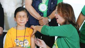 Entinen terveysministeri  Janette Garin antaa denguekuumerokotetta koululaiselle.