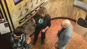 Liminganlahden luontokeskuksen hoitaja Ulla Matturi keskittyy näkövammaisten opastuskierroksella ääniin, näyttelyesineiden kosketteluun ja kerrontaan.